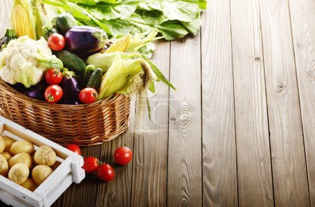 Organic vegetables, food ingredients in basket on wooden background