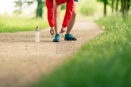 Photo for Woman runner tying sport shoes. Walking or running legs, autumn adventure and exercising outdoors. Motivation and inspiration fitness concept outside. - Royalty Free Image