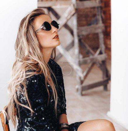 Photo pour Belle jeune femme en robe noire et lunettes de soleil posant - image libre de droit
