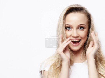 lifestyle and people concept - Beautiful girl surprised and shocked looks on you . Presenting your product. Expressive facial expressions. Studio shoot.