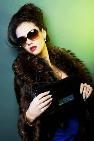 Photo for Beautiful young woman with fashion sunglasses and handbag - Royalty Free Image