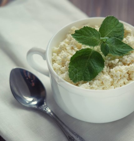 Fresh cottage cheese with mint in a white bowl with spoon on a wooden table. Close up.