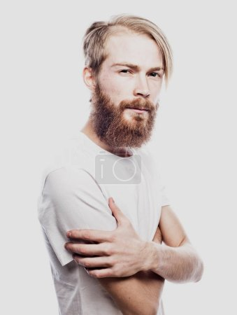 Lifestyle and people concept: Young bearded guy crossing his arms over white background