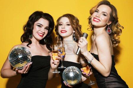 Photo pour Trois joyeuses charmantes jeunes femmes avec des boules disco buvant du champagne et de s'amuser ensemble sur fond jaune - image libre de droit