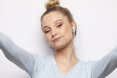 Blond girl in headphones listening music taking photo makes self portrait on smartphone wearing a casual clothes over white background