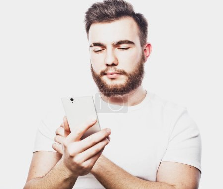 Tehnology and people concept: Bearded man  typing sms on white  background