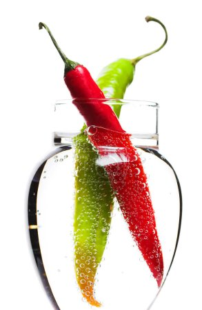 Two Peppers in The Glass of Bubbled Water. Isolated on White in