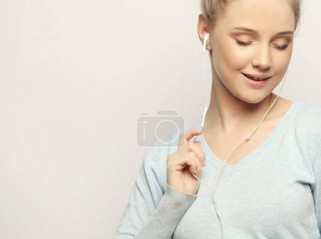 Photo pour Belle jeune femme en casque d'écoute de musique sur fond blanc, gros plan - image libre de droit