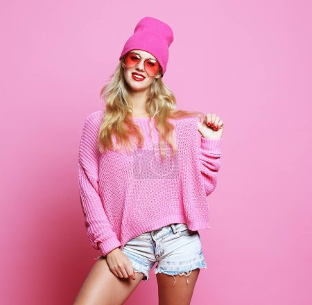Stylish  fashion portrait of trendy casual young woman in pink pulover and  hat,  posing over pink background. Hipster style.