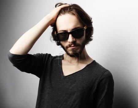 Fashion man wearing fashionable sunglasses on white background