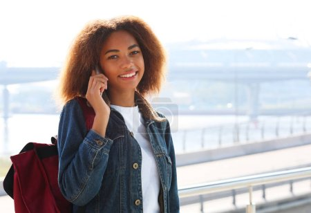 Photo for Beautiful afro american woman using mobile in the street. Communication and lifestyle concept. Summer time. - Royalty Free Image