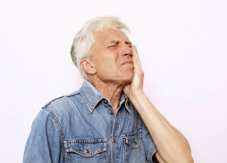Photo pour Problèmes de santé, les gens et la maladie concept - plan en studio de l'homme âgé malheureux appuyant sur la joue en essayant d'apaiser les maux de dents, ayant l'expression douloureuse douloureuse du visage. Sur fond blanc . - image libre de droit