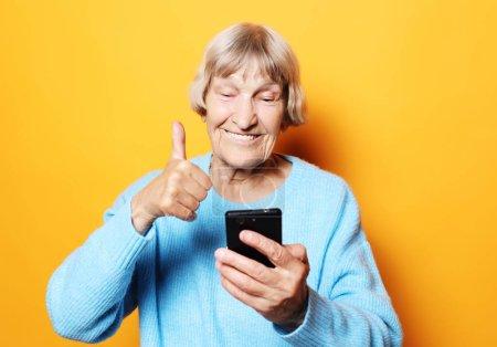 Photo pour Style de vie, concept de famille et de personnes : la vieille grand-mère parle à ses petits-enfants par téléphone, les sourit et les salue.. - image libre de droit