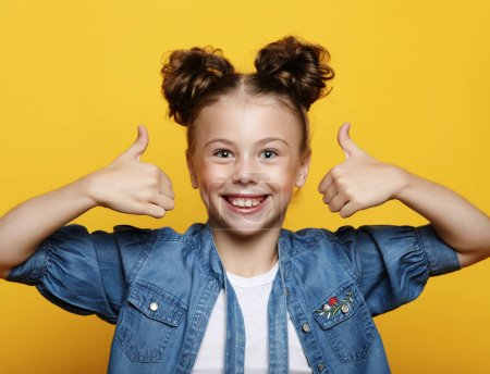 Photo for Emotion, childhood and people concept: Portrait of a beautiful and confident girl showing thumbs up isolated one yellow background - Royalty Free Image