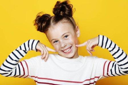 Photo pour Concept d'émotion, d'enfance et de personnes : Portrait d'une petite fille souriante et joyeuse sur fond jaune - image libre de droit