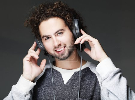 Photo pour Heureux jeune homme souriant à l'écoute de la musique au casque. Sur fond gris. Gros plan. - image libre de droit