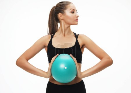 Photo for Sport, fitness and people concept: Athletic woman doing exercise with medicine ball. Photo of sporty woman in fashionable sportswear on white background. - Royalty Free Image