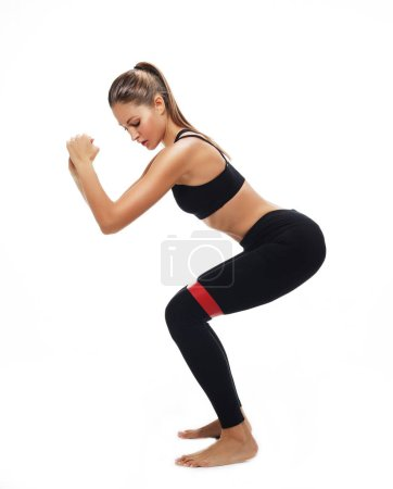 Photo for Motivation, fitness and people concept: Sporty woman  doing a exersize  with resistance band. Photo of young woman in fashionable sportswear on white background. - Royalty Free Image