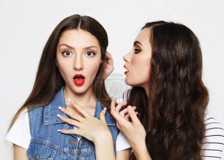 Photo pour Concept de mode de vie, d'émotion et de personnes: Portrait de deux jeunes femmes heureux partage des secrets isolés sur fond blanc - image libre de droit