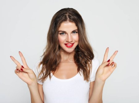 Photo for Lifestyle, emotion and people concept - Portrait of gorgeous woman looking at camera with smile and showing peace sign with fingers - Royalty Free Image