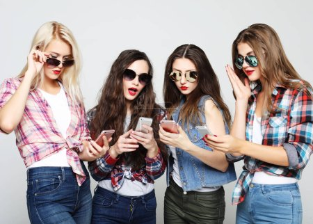 Photo for Tehnology, emotion and people concept: four happy women friends sharing social media in a smart phone, over gray background - Royalty Free Image