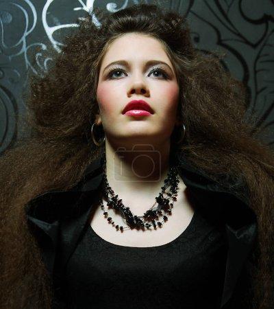 Photo pour Modèle de haute couture en robe noire, avec coiffure créative sur fond noir - image libre de droit