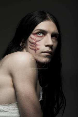 Studio portrait of a young man with paint on his f...