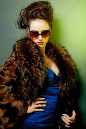 Photo pour Belle jeune femme avec des lunettes de soleil de mode et sac à main - image libre de droit