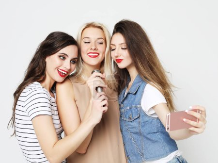 Photo for Lifestyle, happiness, emotional and people concept: beauty girls with a microphone singing and having fun together - Royalty Free Image
