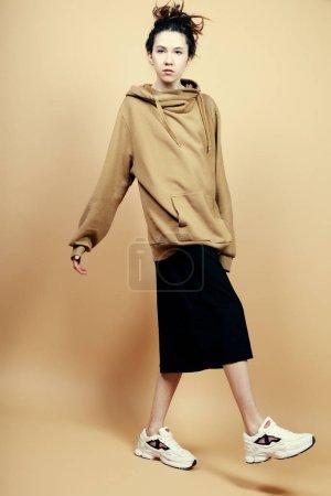 Photo pour Style de vie et concept de mode : belle femme brune portant des vêtements décontractés, posant sur fond beige - image libre de droit