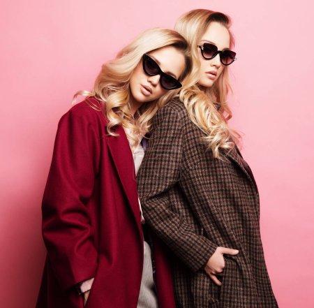 Photo pour Mode deux femmes blondes en manteau avec des lunettes de soleil posant sur fond rose. Mode automne hiver photo. Deux sœurs. - image libre de droit