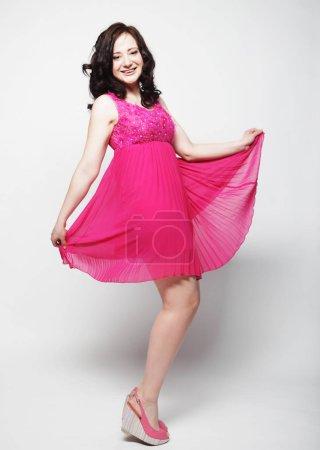 Photo pour Jeune jolie femme aux cheveux bouclés portant une robe rose - image libre de droit