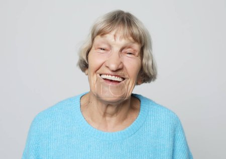 Photo for Lifestyle,emotion and people concept: funny grandmother posing over grey background, close up - Royalty Free Image