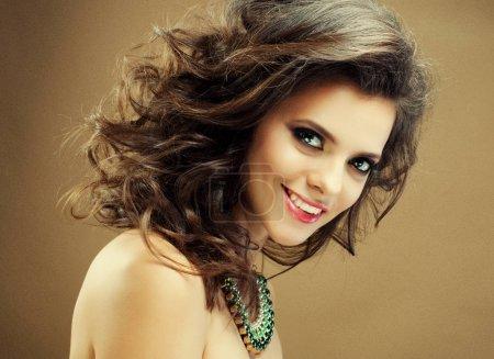Foto de Morena chica con pelo ondulado largo y volulista brillante. Hermoso modelo con peinado rizado, retrato de cerca. - Imagen libre de derechos