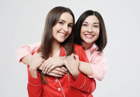Photo pour Style de vie et concept de personnes - deux belles filles habillées en pyjama étreignant et souriant - image libre de droit
