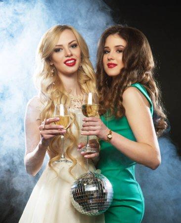 Photo pour Deux jeunes femmes avec verres à vin et boule disco . - image libre de droit