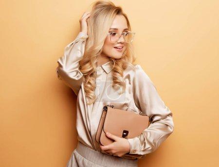 Photo pour Élégante femme blonde en blouse et pantalon posant sur fond beige. Modèle de mode. - image libre de droit