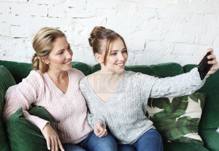 Photo for Portrait of beautiful mature mother and her daughter making a selfie using smart phone and smiling, home and happy. Lifestyle. - Royalty Free Image