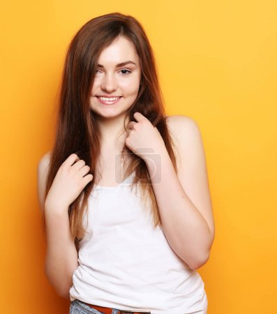 Photo for Portrait of young positive female with cheerful expression, dressed in casual clothes, over yellow background. Beautiful woman indoor. Lifestyle concept. - Royalty Free Image