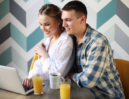 Photo pour Style de vie, tehnology et concept de personnes - Portrait d'un couple riant aimant prendre le petit déjeuner assis à la table dans une cuisine à la maison et regardant ordinateur portable - image libre de droit