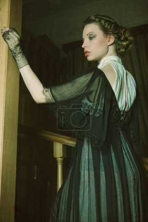 Photo for Beautiful woman in elegant dress posing on stairs - Royalty Free Image