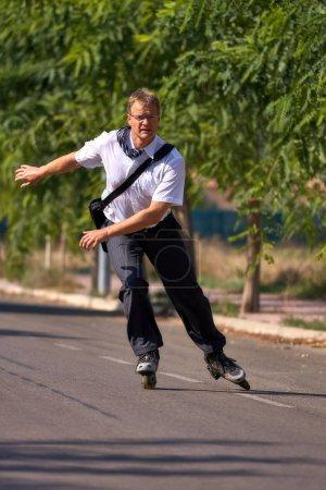 Photo pour Homme d'affaires jeune va pour travailler avec patins, transports alternatifs - image libre de droit