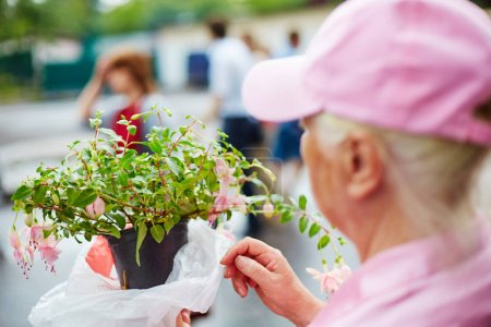 Photo for Grandmother selling a blooming flower in a pot outdoors - Royalty Free Image