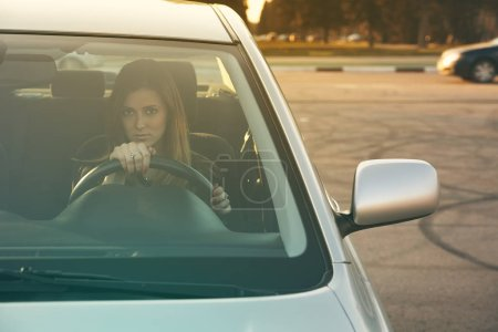 Photo for Young woman driving her car in a driving school. Photo through the windshield - Royalty Free Image