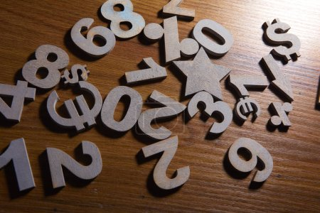 Set of numbers and currency symbols on wooden table, close-up
