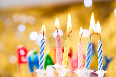 colorful birthday candles on golden background