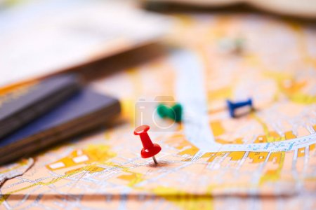 Photo for Pins marking travel itinerary points on map with passports - Royalty Free Image