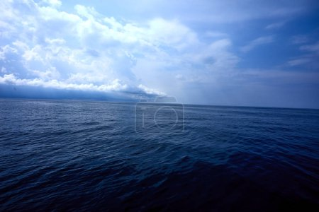 Photo for White fluffy clouds over rippled sea surface - Royalty Free Image