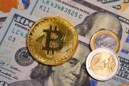 golden bitcoin on dollar banknotes