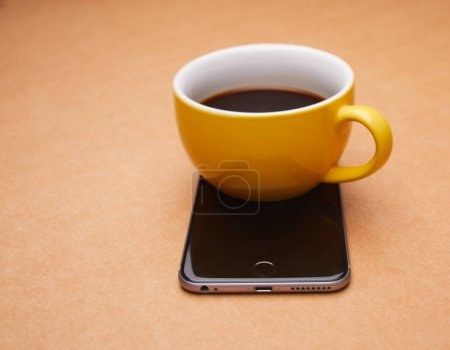 Photo for Yellow cup of coffee on smartphone, close-up - Royalty Free Image